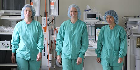 Three perioperative nurses walking down a hallway in the hospital smiling